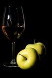 Manzanas y copa de vino verdes con el jugo en negro Fotos de archivo