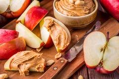 Manzanas y mantequilla de cacahuete rojas para el bocado Imagen de archivo libre de regalías
