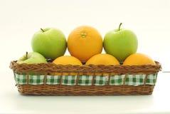 Manzanas y naranjas de una cesta Imagen de archivo libre de regalías