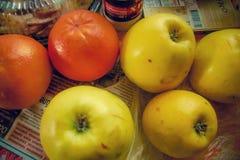Manzanas y naranjas en la tabla con el pueblo del periódico imagen de archivo