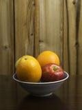 Manzanas y naranjas en un cuenco japonés azul Fotografía de archivo libre de regalías