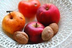 Manzanas y nueces rojas y anaranjadas en una placa de mimbre plástica blanca Humor del otoño, concepto de la cosecha Foto de archivo