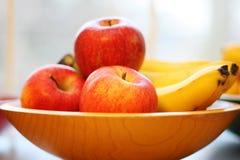 Manzanas y plátanos en un cuenco de madera Imagen de archivo