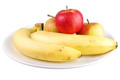Manzanas y plátanos frescos en una placa blanca con el fondo blanco Imagen de archivo