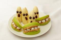 Manzanas y plátanos sanos de los bocados de Halloween en la placa blanca Imagenes de archivo