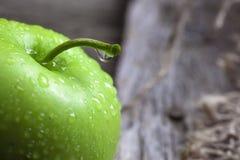 Manzanas y rebanadas verdes maduras de la manzana en gris de madera Fotografía de archivo libre de regalías