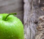 Manzanas y rebanadas verdes maduras de la manzana en gris de madera Fotografía de archivo
