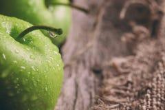Manzanas y rebanadas verdes maduras de la manzana en gris de madera Fotos de archivo libres de regalías