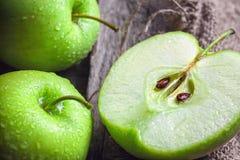 Manzanas y rebanadas verdes maduras de la manzana en gris de madera Imagen de archivo