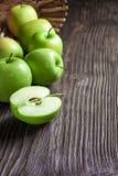 Manzanas y rebanadas verdes maduras de la manzana en gris de madera Imágenes de archivo libres de regalías
