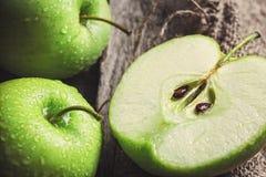 Manzanas y rebanadas verdes maduras de la manzana en gris de madera Imagenes de archivo