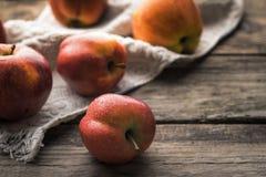 Manzanas y toalla rojas en los viejos tableros Imágenes de archivo libres de regalías