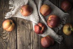 Manzanas y toalla rojas en los viejos tableros Imagen de archivo