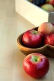 Manzanas y uvas en una caja de madera, cierre para arriba, foco selectivo Imagen de archivo libre de regalías