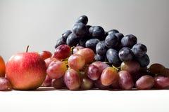 Manzanas y uvas rojas maduras en fondo gris Imagenes de archivo