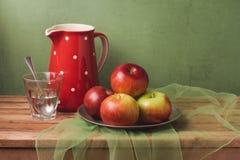 Manzanas y vidrio de agua en la tabla de madera sobre fondo rústico Aún vida retra artística Imagen de archivo
