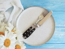 Manzanilla, placa, bifurcación, abastecimiento del verano de la cena del cuchillo de la celebración en un fondo de madera azul Fotos de archivo libres de regalías