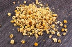 Manzanilla secada en la tabla de madera, medicina alternativa Imágenes de archivo libres de regalías