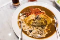Manzo del curry e del riso avvolto in omelette e completato con una salsa di funghi cremosa fotografia stock