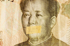 Mao portrait, leader of China with closed mouth on a banknote of Chinese Yuan, as a symbol of the instability of economy. Mao portrait, leader of China with royalty free stock photography