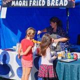 Maori τηγανισμένο ψωμί που προετοιμάζεται για δύο νέους πελάτες από έναν εύθυμο κάτοχο στάβλων αγοράς, Νέα Ζηλανδία στοκ φωτογραφίες