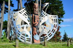Papamoa Domain, Papamoa, New Zealand – December 22, 2018: Maori sculpture, wood and steel, against bright blue sky stock image