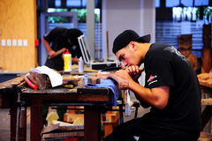 A Maori craftsmen is concentrating on work Stock Photos