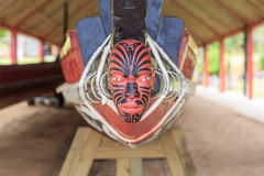 Maori head on a boat. A typical maori puppet head with moko at the end of a war canoe in Waitangi, New Zealand stock photography