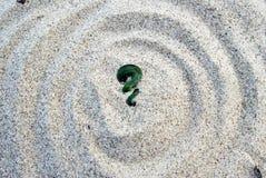 Maori koru fern green stone on sand Royalty Free Stock Photos