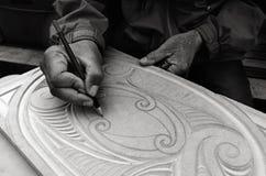 Maori- Mann übergibt Zeichnungsmuster von Maori Wood-Schnitzen Lizenzfreies Stockfoto