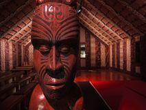 New Zealand: native Maori meeting house. Maori meeting house marae with carved wooden head post royalty free stock photo