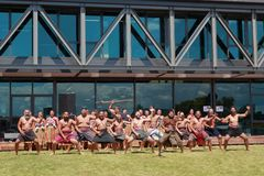 Maori men performing haka outside large modern building. A kapa haka, or Maori dance group, wearing traditional clothing and performing outside a building in stock photo
