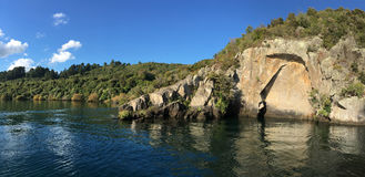 Maori Rock Carving at lake Taupo New Zealand. Panoramic landscape view of the Maori Rock Carving at lake Taupo in the North Island of New Zealand Stock Photography