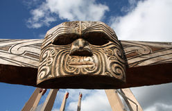 Maori tribal art. Maori carving - face mask carved in the wood. Rotorua, New Zealand Stock Photos