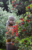 Maori wooden sculpture in red. Maori wooden sculpture covered with red flower on New Zealand Royalty Free Stock Photos