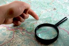 Map. Hand and magnifying glass on background of the map royalty free stock image
