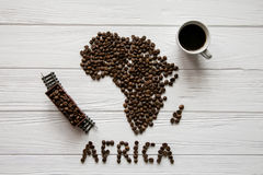 Map of the Africa made of roasted coffee beans laying on white wooden textured background with cup of coffee, toy train Royalty Free Stock Images