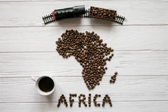 Map of the Africa made of roasted coffee beans laying on white wooden textured background with cup of coffee, toy train Stock Images