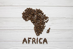 Map of the Africa made of roasted coffee beans laying on white wooden textured background Royalty Free Stock Photos
