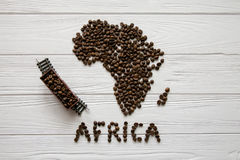 Map of the Africa made of roasted coffee beans laying on white wooden textured background with toy train. Map of the South Africa made of roasted coffee beans Stock Images