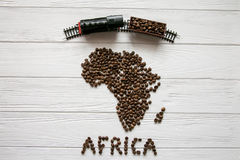 Map of the Africa made of roasted coffee beans laying on white wooden textured background with toy train. Map of the South Africa made of roasted coffee beans Royalty Free Stock Photography