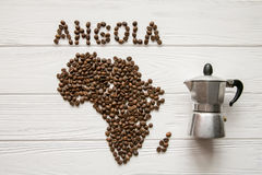 Map of the Angola made of roasted coffee beans laying on white wooden textured background with coffee maker. And space for text Royalty Free Stock Image