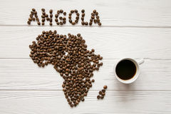 Map of the Angola made of roasted coffee beans laying on white wooden textured background with cup of coffee. And space for text Royalty Free Stock Photos