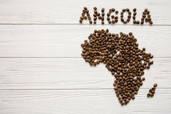Map of the Angola made of roasted coffee beans laying on white wooden textured background. And space for text Royalty Free Stock Image