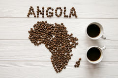 Map of the Angola made of roasted coffee beans laying on white wooden textured background with two cups of coffee. And space for text Stock Images