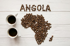Map of the Angola made of roasted coffee beans laying on white wooden textured background with two cups of coffee. And space for text Stock Photography