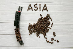 Map of the Asia made of roasted coffee beanMap of the Asia made of roasted coffee bes laying on white wooden textured background. Map of the Asia made of roasted Stock Photography