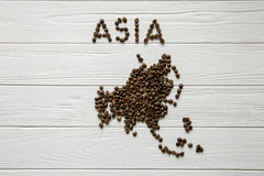 Map of the Asia made of roasted coffee beans laying. On white wooden textured background Royalty Free Stock Images