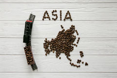 Map of the Asia made of roasted coffee beans laying. On white wooden textured background Royalty Free Stock Image