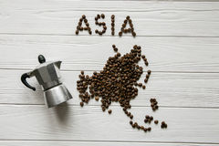 Map of the Asia made of roasted coffee beans laying on white wooden textured background Stock Photo